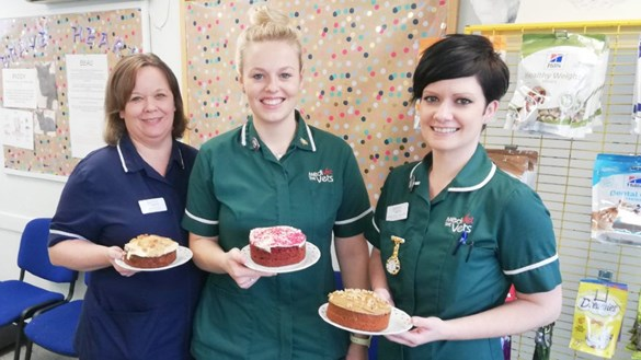 Staff showing off their baked cakes