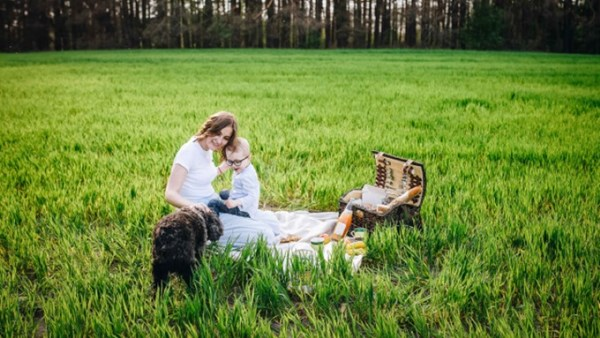 Family picnic with dog in field